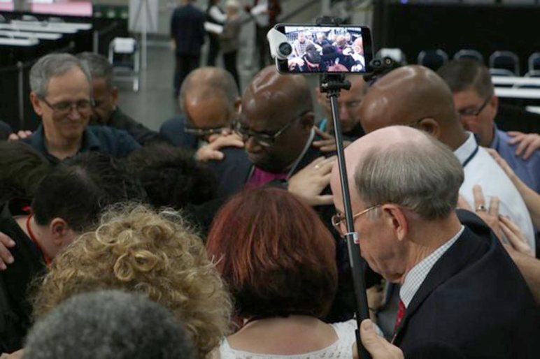 Delegates lay hands on Bishop Palmer